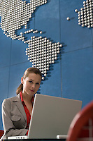 Business woman using laptop in office with world map on wall portrait