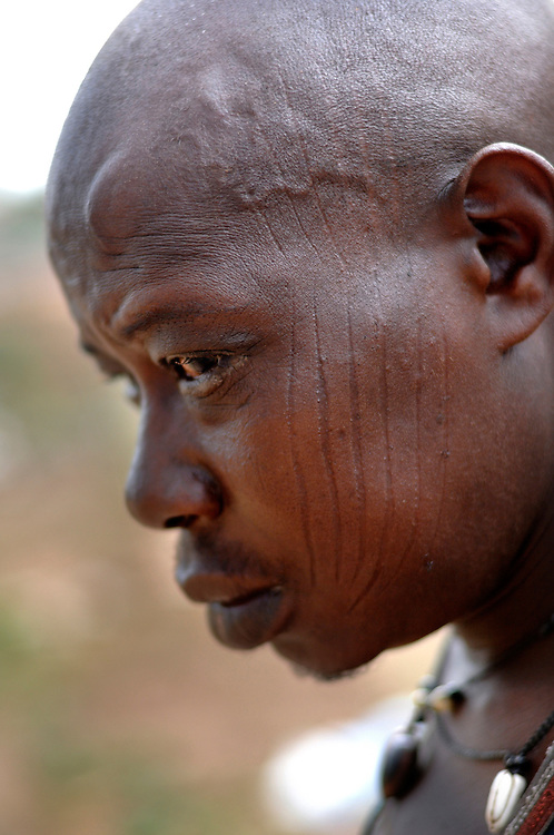 Benin,  Natitingou April 19, 2005 - Man with tribal scarification on his face. Scarification is used as a form of initiation into adulthood, beauty and a sign of a village, tribe, and clan.