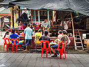 "30 JUNE 2016 - BANGKOK, THAILAND: Workers relax before the evening Chinese opera performance at Chiao Eng Piao Shrine in Bangkok. Chinese opera was once very popular in Thailand, where it is called ""Ngiew."" It is usually performed in the Teochew language. Millions of Chinese emigrated to Thailand (then Siam) in the 18th and 19th centuries and brought their culture with them. Recently the popularity of ngiew has faded as people turn to performances of opera on DVD or movies. There are about 30 Chinese opera troupes left in Bangkok and its environs. They are especially busy during Chinese New Year and Chinese holidays when they travel from Chinese temple to Chinese temple performing on stages they put up in streets near the temple, sometimes sleeping on hammocks they sling under their stage.       PHOTO BY JACK KURTZ"