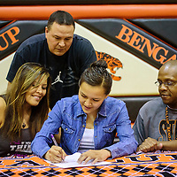 042115  Adron Gardner/Independent<br /> <br /> <br /> Gallup Bengal Kristen Quigley is surrounded by mother Lisa, left, her father Jody and varsity girls basketball coach Kamau Turner as she signs a letter of intent to play for Scottsdale Community College at Gallup High School Tuesday.