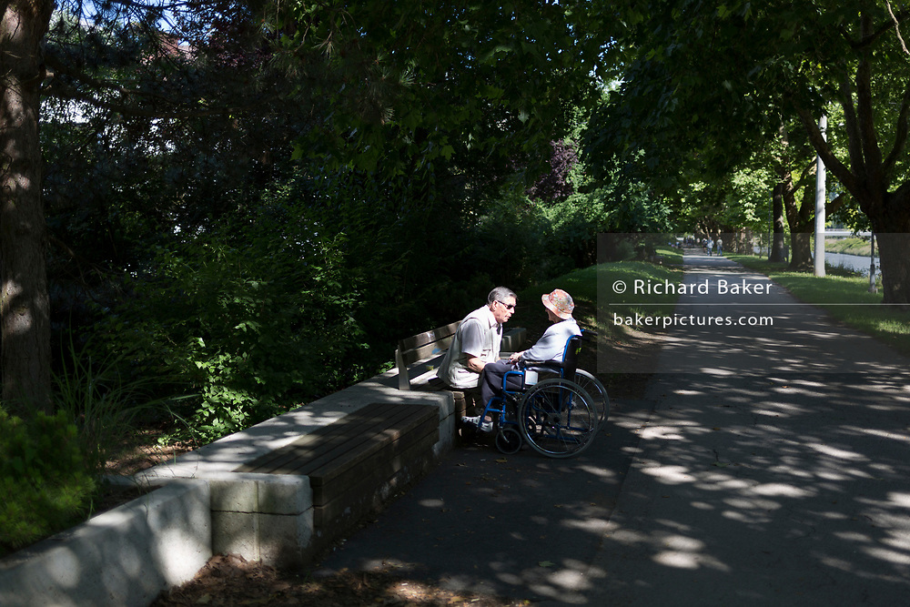 An elderly couple speak with each other on the path edging the Savinja River, on 23rd June 2018, in Celje, Slovenia.