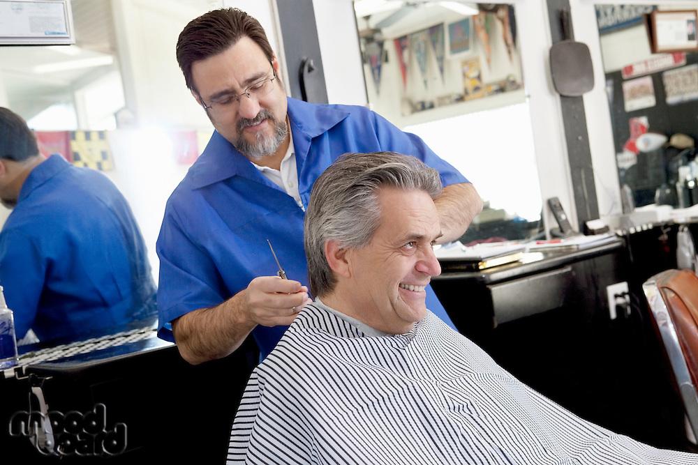 Happy mature man getting a haircut in barbershop