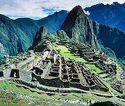 "Machu Picchu is a magnificent Inca archeological site in the Cordillera Vilcabamba, Andes mountains, Peru, South America. A long stairway climbs along Inca walls. Machu Picchu was built around 1450 AD as an estate for the Inca emperor Pachacuti (14381472). Spaniards passed in the river valley below but never discovered Machu Picchu during their conquest of the Incas 1532-1572. The outside world was unaware of the ""Lost City of the Incas"" until revealed by American historian Hiram Bingham in 1911. Machu Picchu perches at 2430 meters elevation (7970 feet) on a well defended ridge 450 meters (1480 ft) above a loop of the Urubamba/Vilcanota River ( Sacred Valley of the Incas). UNESCO honored the Historic Sanctuary of Machu Picchu on the World Heritage List in 1983.  Panorama was stitched from 3 overlapping photos. Published in 2009 on Swedish trekking company site www.adventurelovers.se."