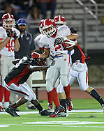 Washington's Joseph McBride (21) is hit by Linn-Mar's Brandon Jeffries (5) and Mason Renner (19) during the second quarter of the game between Cedar Rapids Washington and Linn-Mar at Linn-Mar Stadium in Marion on Friday, September 14, 2012.