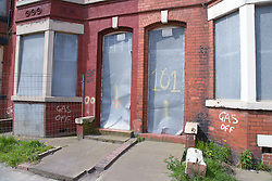 Metal shutters on derelict house with sign indicating that the gas has been disconnected in preparation for demolition as part of the pathfinder regeneration scheme Bootle; Liverpool; England,