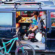 L-R Heather Goodrich and Courtney Gauthier tailgate in the VW van after riding at Friday Night Bikes in Jackson, Wyoming.