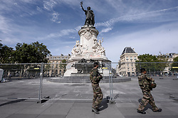 Soldiers walk by city employees as they clean graffitis of the statue of Place de la Republique in Paris, on August 2, 2016 which had become a makeshift memorial in tribute to the victims of the recent attacks of the last two years. The City of Paris began on August 1, 2016 a large cleaning operation of the statue in the center of the square of the Republic, whose pedestal has become after each terrorist attack where people deposited flowers, candles or poems in tribute and support. Archivists of the city, as they have done several times in recent months, had to first select the last objects or documents and photograph texts, drawings, graffiti, related to the attacks, before scanning to preserve those testimonies. Photo by Eliot Blondet / ABACAPRESS.COM