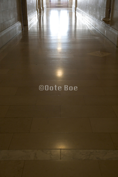 light from the window at the end of the long hall reflecting on a shiny marble floor