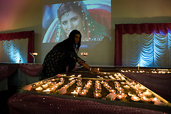 © London News Pictures. 13/11/2011. Harrow, UK.  Sneha Indocha, cousin and best friend of Anni Dewani lighting a candle. Family and friendsmark the first anniversary of her death by holding a candle light vigil at Shree Kadwa Patidar Samaj Community Centre in Harrow, North London today (13/11/2011). Vigils also took place in Anni's home town of Mariestad, Sweden, Bristol and in Cape Town. Anni Dewani was shot in an apparent carjacking while on her honeymoon in Cape Town, South Africa. Anni Dewani's husband Shrien Dewani, who claimed to have been thrown out of the car, has been accused of ordering her murder, and is currently fighting extradition to South Africa to face trial. Photo Credit : Ben Cawthra/LNP
