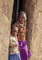 Masai children in the doorway of their boma, Masai Mara, Kenya