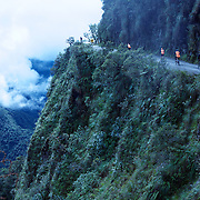 "Mountain Biking on Death Road, Bolivia...A tour group of Mountain Bikers bike down the infamous narrow dirt road, most of the road no wider than 3.2 meter's, is cut into the side of the mountain with sheer drops to the left of up to 600 meter's with virtually no safety rails on the winding steep decent...The North Yugas Road is a 64 Kilometer road leading from La Paz to Corioico. It is legendary for it's extreme danger and in 1995 the Inter American Development Bank christened is as the ""world's most dangerous road"".. The road was built in the 1930's during the Chaco War by Paraguayan prisoners to connect the Amazon rainforest region of Northern Bolivia to it's capital City La Paz. One estimate is that 200 to 300 travelers were killed yearly along the road. On 24 July 1983, a bus veered off the Yungas Road and into a canyon, killing more than 100 passengers in what is said to be Bolivia's worst road accident..A new stretch of the La Paz-Coroico highroad was opened in 2006 to bypass the notorious stretch known as death road..The danger of the road has now made it a popular tourist destination starting in the 1990's and drawing thrill-seekers and mountain bike enthusiasts who ride on the 64km mainly downhill stretch from La Cumbre, a 4,700 meter peak to Yolosa, a decent of 3600 meter's (11,800 feet). The journey includes breathtaking views of snow covered peaks and towering cliffs and starts along modern asphalted road before entering the jungle itself and the most dangerous and notorious part of the ride. The infamous narrow dirt road, most of the road no wider than 3.2 meter's, is cut into the side of the mountain with sheer drops to the left of up to 600 meter's with virtually no safety rails on the winding steep decent..There are now many tour operators catering to this activity, providing information, guides, transport and equipment. Nevertheless, the Yungas Road remains dangerous. At least 13 of these cyclists died on the ride since 1998, the latest A 28-year-ol"