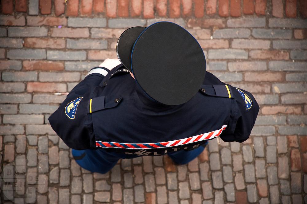 Een agent staat op de Lijnmarkt in Utrecht.<br /> <br /> A policeman is watching at the Lijnmarkt in Utrecht