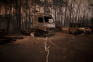 LEIRIA, PORTUGAL - JUNE 18:  Burned vehicles stand near the road after a wildfire took dozens of lives on June 18, 2017 near Castanheira de Pera, in Leiria district, Portugal. On Saturday night, a forest fire became uncontrollable in the Leiria district, killing at least 62 people and leaving many injured. Some of the victims died inside their cars as they tried to flee the area.  (Photo by Pablo Blazquez Dominguez/Getty Images)