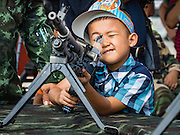 09 JANUARY 2016 - BANGKOK, THAILAND: A Thai boy plays with an Army machine gun during Children's Day festivities at the Royal  Thai Army's Palace Guard, 2nd Division Cavalry Base in Bangkok. National Children's Day falls on the second Saturday of the year. Thai government agencies sponsor child friendly events and the military usually opens army bases to children, who come to play on tanks and artillery pieces.         PHOTO BY JACK KURTZ