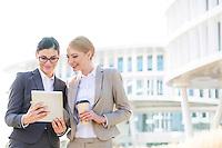 Happy businesswomen using digital tablet outside office building