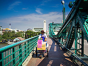 28 OCTOBER 2014 - BANGKOK, THAILAND:  A vendor pushes his cart across Memorial Bridge over the Chao Phraya River in Bangkok. The bridge connects the Bangkok and Thonburi sides of the river.  PHOTO BY JACK KURTZ
