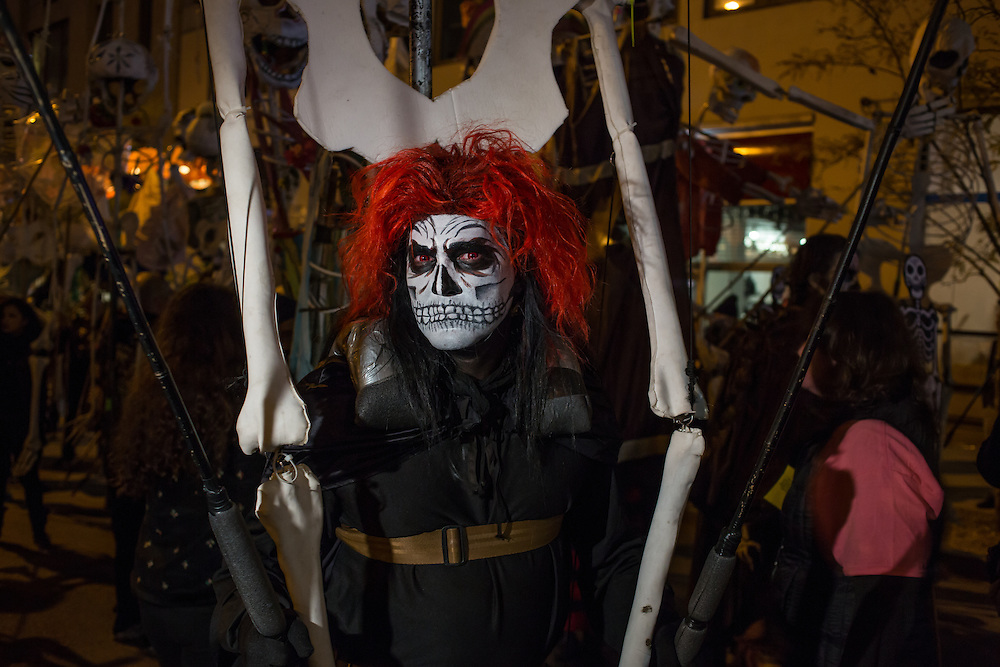 New York, NY - October 31, 2015. A man in a death's head mask carrying a skeleton.