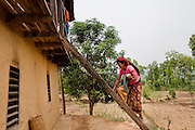 Nisha Darlami's mother carries her 1 month old baby girl, Bushpa, up the stairs to her bedroom in Kalyan Village, Surkhet district, Western Nepal, on 30th June 2012. Nisha eloped with her step nephew when she was 13 but the couple used contraceptives for the next 6 years to delay pregnancy until she turned 18. Now 19, she has a one month old baby girl named Bushpa (flower). In Surkhet, StC partners with Safer Society, a local NGO which advocates for child rights and against child marriage. Photo by Suzanne Lee for Save The Children UK