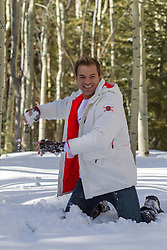man throwing a snowball in the woods