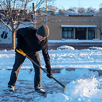 Aaron Morgan, 24, braves the cold tempertures Wednesday evening to start clearing the snow at the skate park in Gallup so him and his friends can get back to skating.