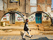 01 MARCH 2017 - BUNGAMATI, NEPAL: A man walks past temporary shelters that have taken on an air of permanence after homes in Bungamati were destroyed in the 2015 earthquake. Recovery seems to have barely begun nearly two years after the earthquake of 25 April 2015 that devastated Nepal. In some villages in the Kathmandu valley workers are working by hand to remove ruble and dig out destroyed buildings. About 9,000 people were killed and another 22,000 injured by the earthquake. The epicenter of the earthquake was east of the Gorka district.     PHOTO BY JACK KURTZ