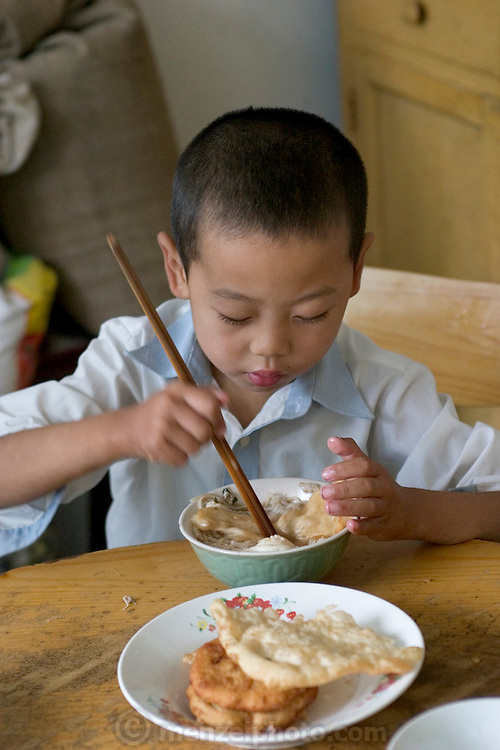 (MODEL RELEASED IMAGE). Cui Yuqi, 6, eats breakfast at the Cuis'. Today breakfast includes fresh eggs from the family hens and hot mian tiao (noodles) with a little cooked spinach and MSG. (Supporting image from the project Hungry Planet: What the World Eats.) The Cui family of Weitaiwu village, Beijing Province, China, is one of the thirty families featured, with a weeks' worth of food, in the book Hungry Planet: What the World Eats.