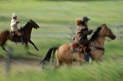 North America, United States, Montana, Boulder River Valley, two wranglers on horseback (blurred motion)