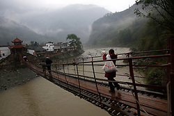 Chinese residents carry supplies across a bridge in Yuxi Village of Lushan County, Sichuan Province, China, 23 April 2013. Landslides and fallen rocks block vital roads carrying supplies to remote towns and villages affected by the earthquake. The Lushan Earthquake in Sichuan Province on 20 April 2013 resulted in 186 people dead, 21 missing, 11248 injured. About 1.72 million people were affected by the quake, while an initial estimate by the International Red Cross on Saturday put the number needing emergency shelter, water and food at 120,000. The China Earthquake Administration (CEA) recorded a magnitude 7.0 earthquake, while the US Geological Survey said it had measured 6.9.
