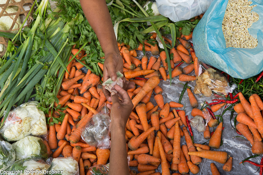 Customers pick and pay for carrots at the market in Mulo, Wonosari subdistrict, Gunung Kidul district, Yogyakarta Special Region, Indonesia.