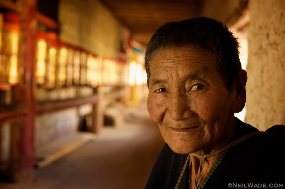This elderly Tibetan woman is taking a break from walking koras - circles walked around a religious monument.  Dawu (Dafu), Tibet (China).