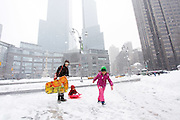 kids play in the snow at the entrance to central park on February 26,  2009 in New York City. photo by Joe Kohen for The New York Times