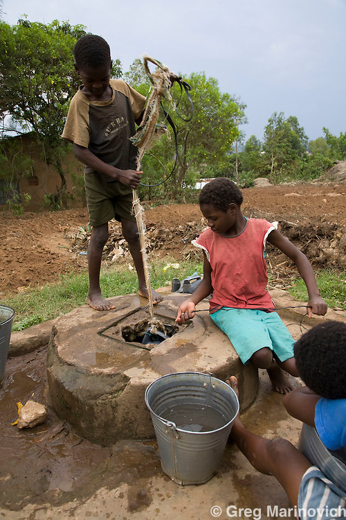 Maurice and other oprhaned children draw water from a well in Limbe. Marie da Silva started Jacaranda, a free school for Aids orphans, in her home town of Limbe, near Blantyre, Malawi, after her father and another 13 of her family died of Aids. She has funded it by donating a third of her salary as a nanny in the USA. There are over 200 children and they have been schooling in her late mother's house, but donations after being nominated as a CNN Hero have enabled her to build a proper school building, which she opened on her 50th birthday. Oct 2008. Photo Greg Marinovich