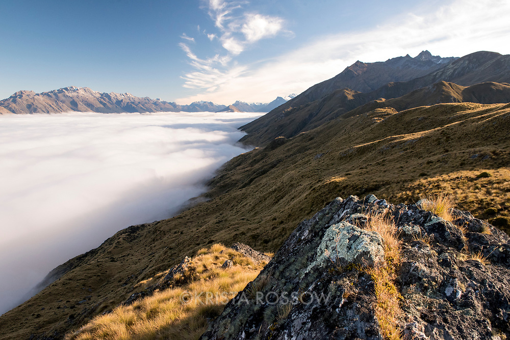 Mid-morning scene on a mountaintop near Mount Creighton above the cloud-covered Lake Wakatipu near Queenstown on the South Island of New Zealand.