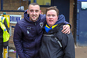AFC Wimbledon midfielder Dylan Connolly (16) posing with fan after win during the EFL Sky Bet League 1 match between Southend United and AFC Wimbledon at Roots Hall, Southend, England on 16 March 2019.