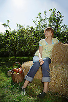 Woman sitting on hay bales near orchard