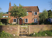 Property released picture of red brick detached house viewed from front wall and gate, Shottisham, Suffolk, England