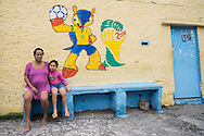 A mother and her daughter sit on a bench in front of a FIFA World Cup 2014 mural at the Santo Amaro favela, Rio de Janeiro, Brazil. According to Patrick Ashcroft an English (Stockport) researcher and teacher who lives in the favela, it is fairly quiet and non violent. There is a heavily armed police presence in the favela.<br /> Picture by Andrew Tobin/Focus Images Ltd +44 7710 761829<br /> 20/06/2014