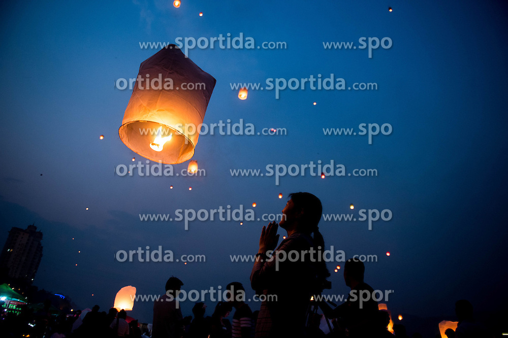 A woman makes a wish after she sets a sky lantern into the air along the Lancang River in Jinghong City, southwest China's Yunnan Province, April 13, 2016, to celebrate the new year on the calendar of the Dai ethnic group. EXPA Pictures © 2016, PhotoCredit: EXPA/ Photoshot/ Hu Chao<br /> <br /> *****ATTENTION - for AUT, SLO, CRO, SRB, BIH, MAZ, SUI only*****