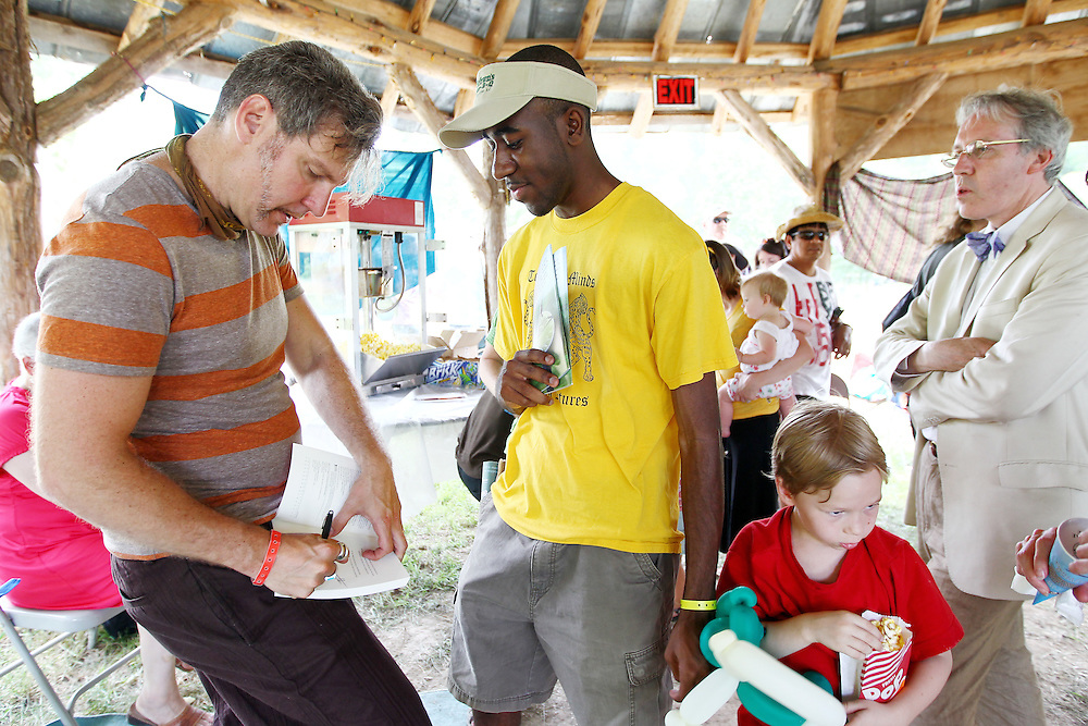 """Mark Scandrette, left, signs a copy of his new book """"Practicing the Way of Jesus"""" at the Wild Goose Festival at Shakori Hills in North Carolina June 25, 2011.  (Photo by Courtney Perry)"""