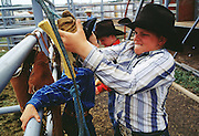 05 AUGUST 2000 - WILLIAMS, AZ: A young cowboy gets his rigging ready before competing at the 22nd Annual Cowpunchers' Reunion Rodeo in Williams, Arizona, Aug 5.  The Cowpunchers' Reunion Rodeo is held for working cowboys from the ranches in Arizona and the region. PHOTO BY JACK KURTZ