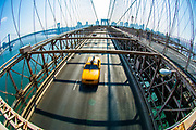 A Yellow Cab taxi on the  Brooklyn Bridge between Manhattan and Brooklyn over the East River. New York