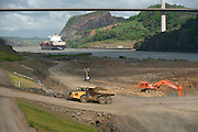 Cargo ship passing nearby excavation works of Panama Canal expansion project. Panama City, Panama, Central America.