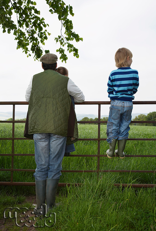 Father with two children (5-6) standing by fence in countryside
