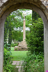 Looking through stone arch into Armillary Court at Snowshill Garden