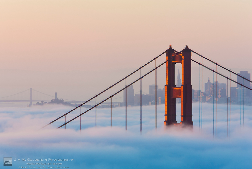 First light illuminates a fog shrouded Golden Gate Bridge and San Francisco skyline at sunrise