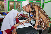 "Sept. 29, 2009 -- SAI BURI, THAILAND: A teacher in an Islamic studies class at the Darunsat Wittya Islamic School in Sai Buri, Thailand. The school is the largest Muslim high school in Pattani province. Although it is a private school, the Thai government pays students' tuition to attend the school. The curriculum combines Thai official curriculum with Islamic curriculum. Many of the students go on to college level education in Egypt and Saudi Arabia. The Thai government views Islamic high schools with suspicion, fearing they radicalize students. Thailand's three southern most provinces; Yala, Pattani and Narathiwat are often called ""restive"" and a decades long Muslim insurgency has gained traction recently. Nearly 4,000 people have been killed since 2004. The three southern provinces are under emergency control and there are more than 60,000 Thai military, police and paramilitary militia forces trying to keep the peace battling insurgents who favor car bombs and assassination.   Photo by Jack Kurtz / ZUMA Press"
