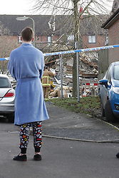 © Licensed to London News Pictures. 27/12/2018. Andover, UK. A resident stands in dressing down and slippers as he looks at the remains of a house in Andover, Hampshire where a mans body has been pulled from wreckage, following an explosion at a house. Residents have been evacuated form the area following a blast in the early hours of this morning. Photo credit: Peter Macdiarmid/LNP