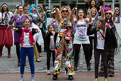 © Licensed to London News Pictures. 18/05/2013. London, UK. Demonstrators from the No More Page 3 campaign perform a 1970's themed flash mob outside News International offices in Wapping, East London on 18 May 2013 with their own version of YMCA. The No More Page 3 campaign wants Dominic Mohan, Editor of The Sun newspaper, to stop using photos of topless female models in the daily newspaper. Photo credit : Vickie Flores/LNP