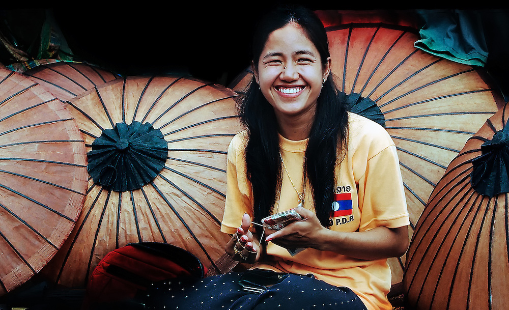 A woman selling hand made paper umbrellas in a street market in Luang Prabang, Laos.