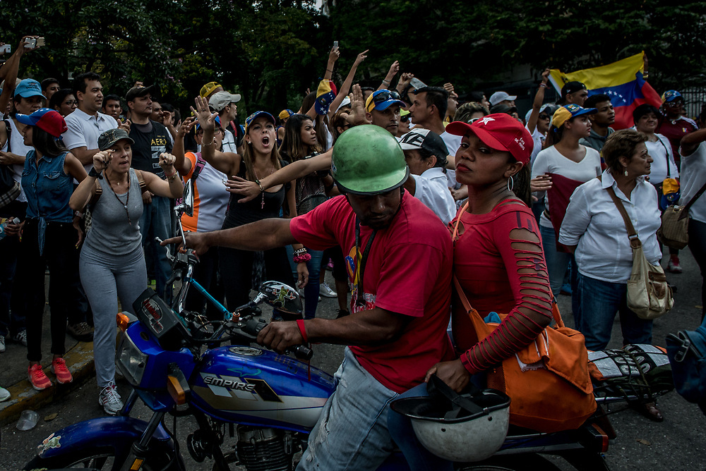 "CARACAS, VENEZUELA - APRIL 19, 2017:  Opposition protesters in ""La Vega"" slum in Caracas shout ""We're here because we want to be, not becuase we were paid to be!"" at passing government supporters, dressed in red on a motorcycle. Government supporters also held a march today.  Hundreds of protesters showed up in La Vega slum, many more than were present supporting the opposition.  Several people present said they were obligated by the government to attend in order to keep their jobs and access to government subsidized food and housing.   This protest was significant, because it was the firt time that a significant people from the slums came down to join an opposition march, which usually consists of middle-class protesters.   PHOTO: Meridith Kohut"